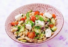 Salada dos feijões brancos, do tomate, do aipo, do pepino, da rúcula, da cebola vermelha e do queijo de feta na bacia Imagens de Stock