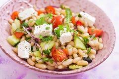 Salada dos feijões brancos, do tomate, do aipo, do pepino, da rúcula, da cebola vermelha e do queijo de feta na bacia Fotos de Stock Royalty Free