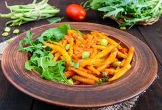 Salada dos feijões verdes, cozidos com as cebolas no molho de tomate e nas folhas verdes da rúcula Fotos de Stock