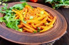 Salada dos feijões verdes, cozidos com as cebolas no molho de tomate e nas folhas verdes da rúcula Fotografia de Stock