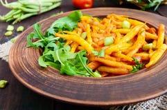 Salada dos feijões verdes, cozidos com as cebolas no molho de tomate e nas folhas verdes da rúcula em uma bacia cerâmica Fotos de Stock