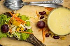 Salada e vinho tinto de milho na colher preta da tabela no assoalho Fotografia de Stock Royalty Free