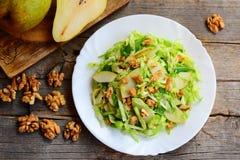 Salada fácil da pera e de couve Salada home com a pera, couve e as nozes cruas frescas em uma placa branca e no fundo de madeira  fotografia de stock royalty free