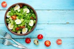 Salada fresca com alface, os tomates de cereja e os ovos de codorniz verdes fotos de stock