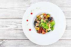 A salada fresca com atum, rúcula, alcachofras, bacalhaus, azeitonas, manjericão, sol secou tomates, tomates de cereja, pepino, co Fotografia de Stock Royalty Free