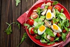 Salada fresca com galinha, tomates, ovos e rúcula na placa foto de stock