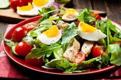 Salada fresca com galinha, tomates, ovos e rúcula na placa Fotos de Stock Royalty Free