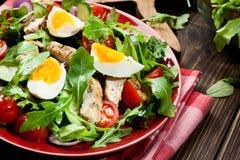Salada fresca com galinha, tomates, ovos e rúcula na placa Fotografia de Stock