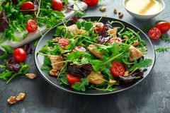 Salada fresca com peito de frango, rúcula, porcas e tomates na placa preta em uma tabela de madeira Imagens de Stock