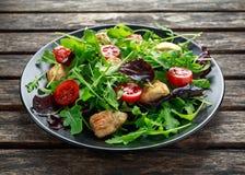 Salada fresca com peito de frango, rúcula, porcas e tomates na placa preta em uma tabela de madeira Fotos de Stock