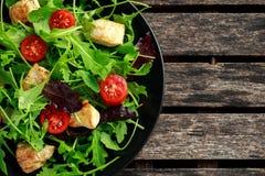Salada fresca com peito de frango, rúcula, porcas e tomates na placa preta em uma tabela de madeira Imagem de Stock Royalty Free