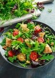 Salada fresca com peito de frango, rúcula, porcas e tomates na placa preta em uma tabela de madeira Fotos de Stock Royalty Free