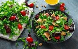 Salada fresca com peito de frango, rúcula, porcas e tomates na placa preta em uma tabela de madeira Imagem de Stock