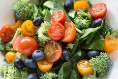 Salada fresca com tomates, espinafres, mirtilos, brocolli e cu Imagem de Stock