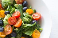 Salada fresca com tomates, espinafres, mirtilos, brocolli e cu Fotos de Stock