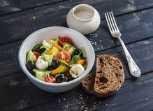 Salada fresca com tomates, pepinos, pimentas, azeitonas, queijo em uma bacia cerâmica e ciabatta do pão de centeio Foto de Stock