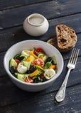 Salada fresca com tomates, pepinos, pimentas, azeitonas, queijo em uma bacia cerâmica e ciabatta do pão de centeio Imagens de Stock