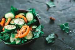 Salada fresca com vegetais em um fundo matte preto O conceito de uma dieta saudável Fotos de Stock Royalty Free