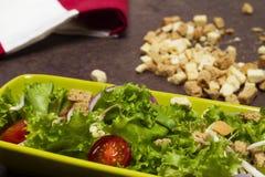 Salada fresca da alface e da cebola do tomate com o pano listrado vermelho, os laços do pão e a colher de madeira foto de stock royalty free