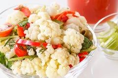 Salada fresca da couve-flor com tomate, brócolis, azeitonas, pimenta doce, ervas, aipo e um vidro do suco de tomate Fotografia de Stock
