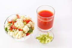 Salada fresca da couve-flor com tomate, brócolis, azeitonas, pimenta doce, ervas, aipo e um vidro do suco de tomate Imagens de Stock Royalty Free