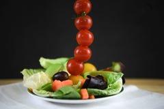 Salada fresca da folha em uma placa com os tomates em uma linha vertical alta com espaço Imagem de Stock