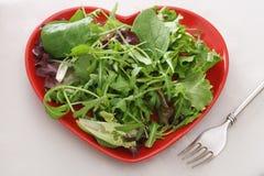 Salada fresca da folha na placa vermelha da forma do coração Fotos de Stock