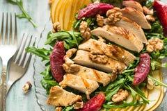 Salada fresca da mola com peito de frango grelhado, rúcula, pera e fatias e nozes alaranjadas imagem de stock royalty free