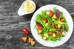A salada fresca de tomates de cereja, pão torrado e ovas do badejo, alface misturada sae no prato branco na tabela de madeira vel Fotos de Stock Royalty Free