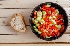 Salada fresca do tomate e do pepino na placa preta no fundo de madeira fotografia de stock royalty free