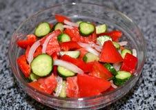 Salada fresca do tomate, do pepino e das cebolas em uma bacia de vidro, alimento da dieta, vegetarianismo fotografia de stock