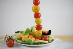 Salada fresca em uma placa com os tomates em uma linha vertical alta Foto de Stock
