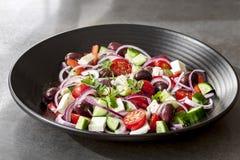 Salada grega na bacia preta Imagens de Stock Royalty Free