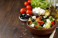 Salada grega saboroso com feta, azeitonas e tomates em uma bacia no fundo de madeira Fotos de Stock Royalty Free
