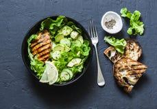 Salada grelhada da galinha, do abacate, do pepino e da alface - saudável, bacia equilibrada do alimento no fundo escuro Imagens de Stock Royalty Free