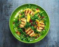 Salada grelhada do queijo de Halloumi com laranja, folhas do foguete, romã e semente de abóbora Alimento saudável Fotografia de Stock Royalty Free