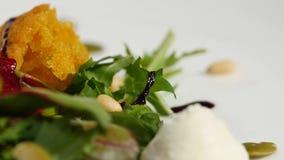Salada italiana da beterraba do assado Salada de beterrabas roasted com queijo e pinhões de cabra no prato branco em um branco Fotos de Stock Royalty Free