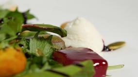 Salada italiana da beterraba do assado Salada de beterrabas roasted com queijo e pinhões de cabra no prato branco isolado em um b Fotos de Stock