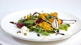 Salada italiana da beterraba do assado Salada de beterrabas roasted com queijo e pinhões de cabra no prato branco isolado em um b Foto de Stock Royalty Free