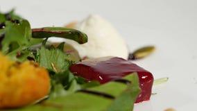 Salada italiana da beterraba do assado Salada de beterrabas roasted com queijo e pinhões de cabra no prato branco isolado em um b Imagem de Stock Royalty Free