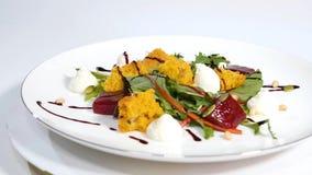 Salada italiana da beterraba do assado Salada de beterrabas roasted com queijo e pinhões de cabra no prato branco isolado em um b Fotos de Stock Royalty Free