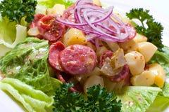 Salada morna com salsichas fritadas cebola e batata, decoradas com alface Fotos de Stock