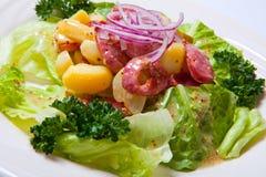 Salada morna com salsichas fritadas cebola e batata, decoradas com alface Foto de Stock Royalty Free