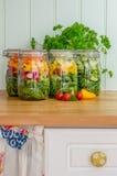 Salada nos frascos de vidro do armazenamento na cozinha Fotografia de Stock