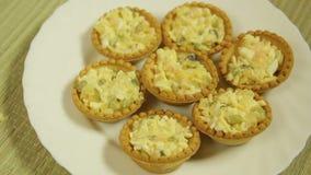 Salada nos tartlets em uma placa branca Close-up filme