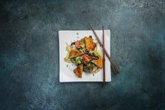 Salada pan-asiático, vegetais com frango frito Em uma placa branca quadrada com hashis Vista superior Imagens de Stock