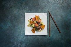 Salada pan-asiático, vegetais com frango frito Em uma placa branca quadrada com hashis Vista superior Fotos de Stock