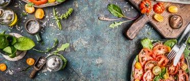 Salada saudável do vegetariano que faz a preparação com os tomates no fundo rústico, vista superior Foto de Stock