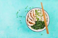 Salada saud?vel em uma bacia branca, hashis Rolos da galinha, arroz, chuka e cebola verde imagens de stock