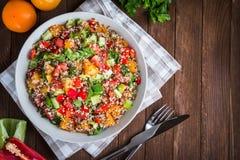 Salada saudável fresca com quinoa, os tomates coloridos, pimenta doce, pepino e salsa na opinião superior do fundo de madeira Fotos de Stock Royalty Free